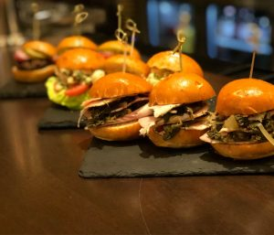 a slate platter filled with small burger slider assortments