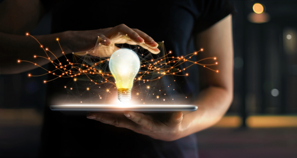 Hands holding tablet with light bulb